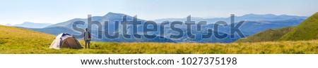 Hiker man standing near camping tent in carpathian mountains. Tourist enjoy mountain view. Travel concept. #1027375198