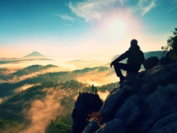 Hiker man take a rest on mountain peak. Man lay on summit, bellow autumn valley. Bright morning Sun shining in sky.
