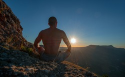 hiker meditate in lotus pose, on beauty mountain landscape background, holiday traveling concept, horizontal photo