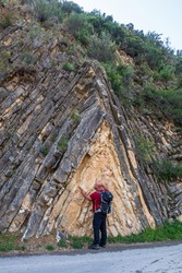 Hiker observing a very curious geological formation called anticline, in Sot de Chera, Valencia (Spain).