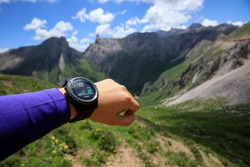 Hiker on high altitude mountain top checking the altimeter on the sports watch