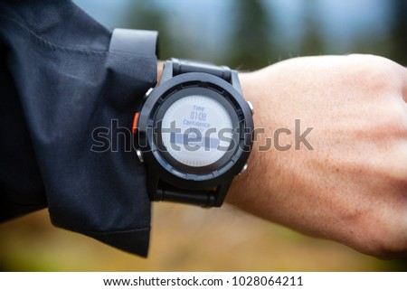 Hiker on mountain trail looking at sportwatch, checking direction on electronic compass, hiking and navigation.