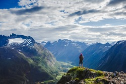 Hiker on the mountain top. Sport and active life concept. Hiking ROMSDALSEGGEN RIDGE, Andalsnes City, Norway
