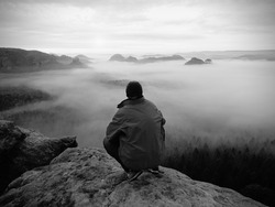 Hiker on the rocky peak. Wonderful daybreak in mountains, heavy  creamy mist in deep valley. Man on the summit. Black and white photo.