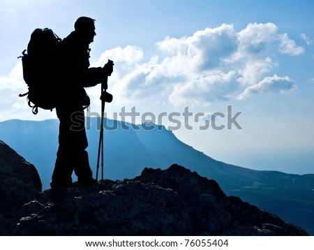Hiker on top, silhouetted in high mountains