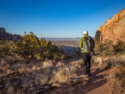 Hiker on Wedding Canyon Trail in Colorado National Monument. Late afternoon.  Grand Junction, Colorado in distance. Red sandstone cliffs. Blue sky