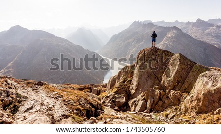 Photo of  Hiker or alpinist at the top of a mountain. A success of mountaineer reaching the summit. Outdoor adventure sports alpine moutain landscape. Sunny day and a adventure man on a top of a peak.