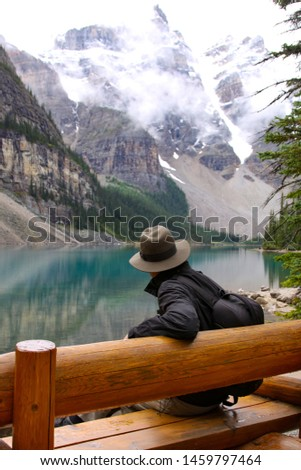 Hiker pauses on wooden bench at Lake Moraine Lake #1459797464