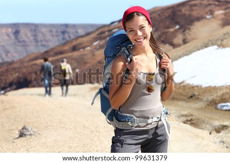Hiker portrait. Female hiking woman happy and smiling during hike trek on volcano Teide, Tenerife, Canary Islands. Beautiful young mixed race Asian Chinese / Caucasian sporty model joyful. - stock photo