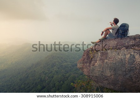 Hiker relaxing on top of the mountain and drinking bottled water