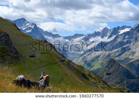 Hiker resting on green grass near ski station Les deux Alpes and view on Alpine mountains peaks in summer, Les Ecrins range, Isere, France Stock fotó ©