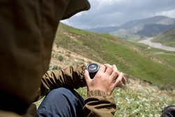 Hiker sit on high altitude mountain top checking the altitude on the sportswatch
