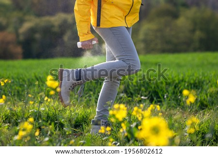 Hiker spray insect repellent against tick and mosquito bite on her legs and boots Photo stock ©