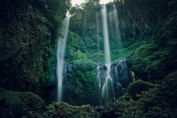 Hiker standing in front of huge Jungle waterfall surrounded by lush jungle vegetation and flora in Bali, Indonesia. Travel survival, lifestyle concept. Beautiful Sekumpul waterfall on Bali
