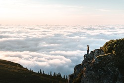 Hiker standing on cliff edge and looking at view on montain summit. Young climber enjoying sunrise or sunset looking at the cloud inversion. Travel, sport and active life concept in Ceahlau Massiff