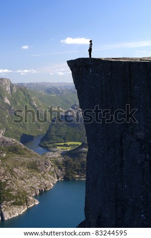 hiker standing on Preikestolen and looking at the sky, Preikestolen - famous cliff at the Norwegian mountains