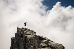 Hiker standing on steep rocky mountain summit without protection. Dramatic cloudy sky. Concept of reaching the goal and conquering the success. Contrasted, silhouette like.