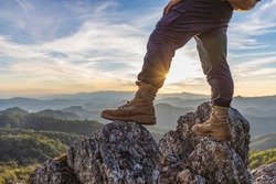 Hiker standing on top mountain sunset background. Hiker men's hiking living healthy active lifestyle.