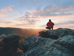 Hiker standing on top of a mountain and enjoying sunrise. Beautiful moment the miracle of nature