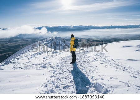 Hiker stands and enjoys valley view from hilly viewpoint. Hiker reached top of the mountain. Adventure ascent of alpine peak in snow