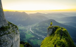 Hiker stands and enjoys valley view from hilly viewpoint. Traveling on hill peaks landscape. Sport, tourism and hiking concept. Watching sunset.