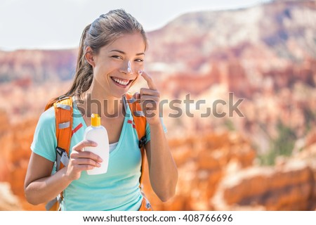 Hiker sunscreen. Woman hiking putting sunblock lotion outdoors during summer hike holidays. Mixed race Caucasian Asian female model.