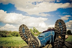 hiker taking a rest on a summer-day.Focus on bottom of hiking-boots.Personal editing velvia filter