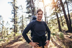 Hiker trekking on the trail in a forest. Smiling man exploring nature walking through the woods.