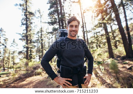 Shutterstock Hiker trekking on the trail in a forest. Smiling man exploring nature walking through the woods.
