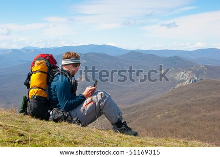 Hiker using mobile device in mountains
