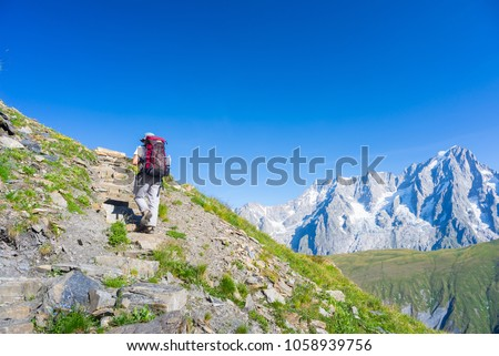 Hiker walking uphill on footpath with great panoramic view over the Mont Blanc massif and mountain peak (4810 m). Backpacker's summer adventures and wanderlust in Valle d'Aosta, Italian French Alps.
