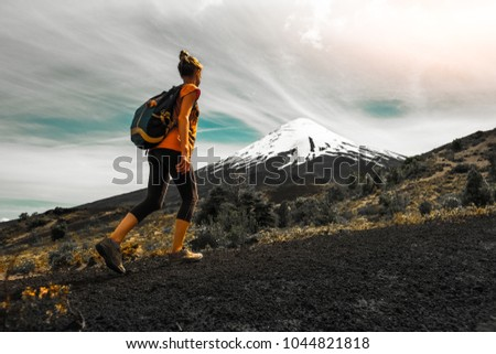 Hiker walks on the slope of volcano. Woman enjoys the trail with views of the volcano of Osorno, Chile