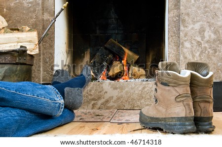 Hiker warming up and relaxing by a small fireplace