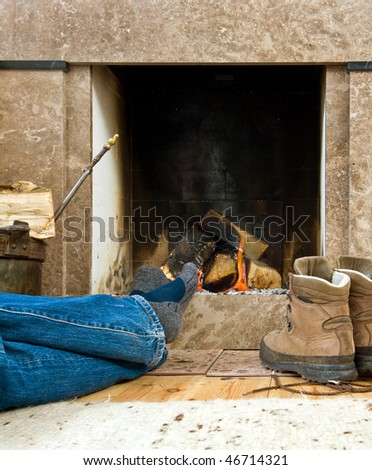 Hiker warming uyp and relaxing by a small fireplace