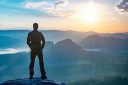Hiker watching to autumn Sun at horizon . Beautiful moment. Spectacular mountain ranges silhouettes. Man reaching summit enjoying freedom