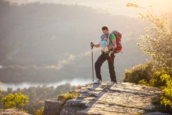 Hiker with baby relaxing on cliff and enjoying valley view.