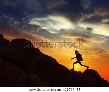 Hiker with backpack jumping over rocks with sunset sky on the background