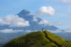 Hiker with backpack looks at the view on the Mayon volcano,Philippines