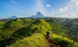 Hiker with backpack looks at the view on the Mayon volcano,Quit in Day Hills area,Philippines