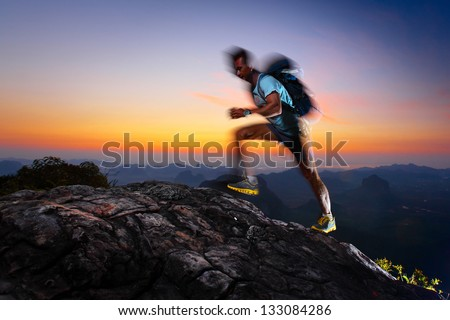 Hiker with backpack reached top of a mountain at sunrise. Motion blurred elements. Feet, hand, shoulder and part of face are in focus.