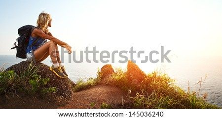 Hiker with backpack relaxing on a rock and enjoying sunset