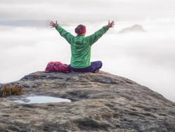 Hiker with backpack sitting  on top of a mountain with raised hands and enjoying sunrise