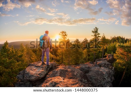 Hiker with backpack standing on a rock and enjoying sunset on mauntain Сток-фото ©