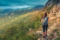 Hiker with backpack standing on top of a mountain. Achievement in mountains. Freedom and active life concept.