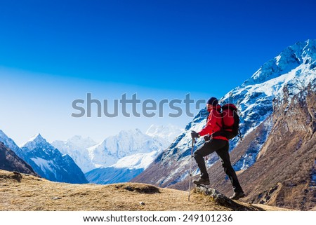 Hiker with backpack standing on top of a mountain and enjoying. Himalayas