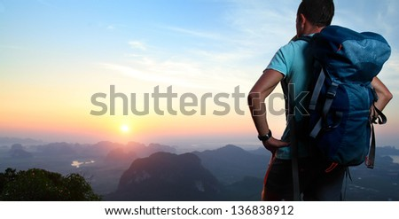 Hiker With Backpack Standing On Top Of A Mountain And Enjoying Sunrise.