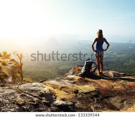 Hiker with backpack standing on top of a mountain and enjoying valley view