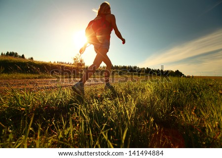 Hiker with backpack walking on a gravel road