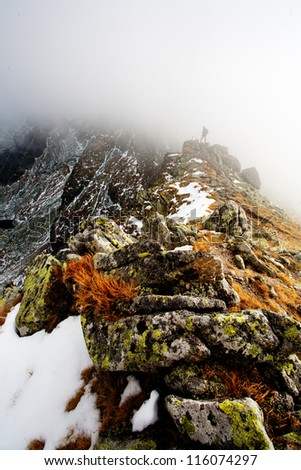 Hiker with backpacks is looking at teh cloudy mountains. Atumn Polish High Tatra Mountains.