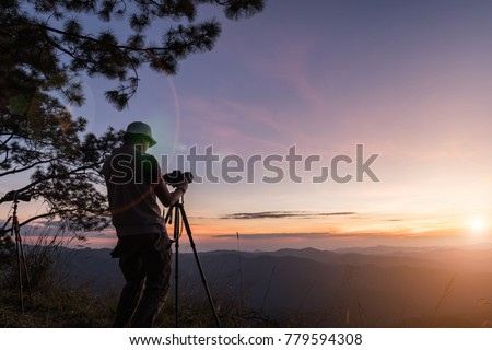 Hiker with camera on tripod takes picture from rocky summit. Thailand.